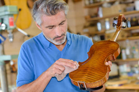 skillful: Instrument maker polishing violin