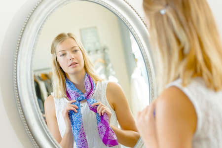 Trying a scarf on in a mirror