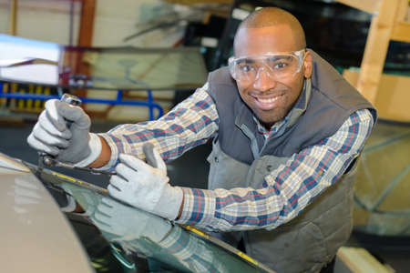 mechanic replacing car windscreen Stock Photo