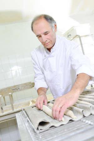 empleada domestica: Preparing baguettes for the oven Foto de archivo