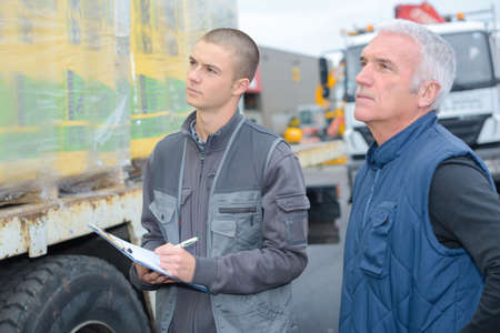 truck driver: Man with clipboard looking at delivery on lorry