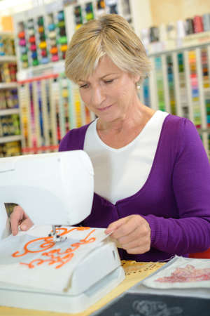 Senior lady using sewing machine Stock Photo