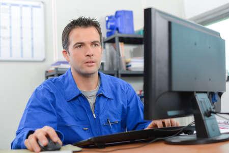 Manual worker sat at his desk
