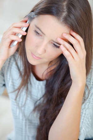 40 something: Woman looks worried during phone call Stock Photo