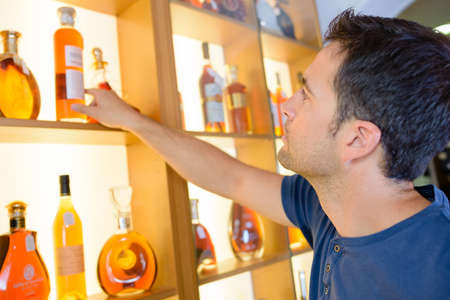 reach customers: Man selecting bottle of brandy from shelf Stock Photo