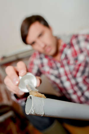 watertight: Man applying glue to end of pvc pipe Stock Photo