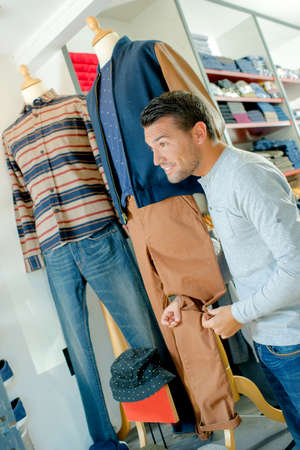 company person: Man in shop holding trouser leg on mannequin
