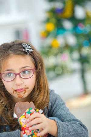 Young girl with messy mouth eating chocolate Stock Photo