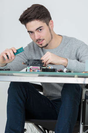 crippled: handicapped electronic parts assembler Stock Photo