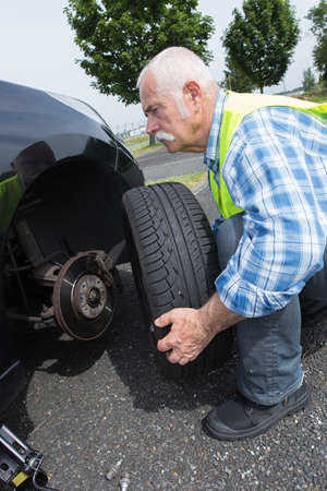 winter tires: aged man changing leaking tire on the verge