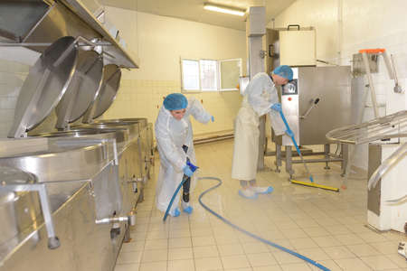 cleaners cleaning industrial kitchen floor