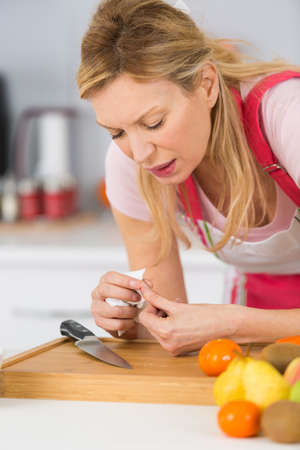 cook woman in red apron cutting and hurting her finger Stock Photo