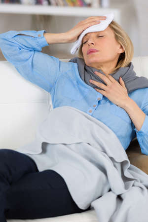 sick woman with headache lying on the sofa Stock Photo