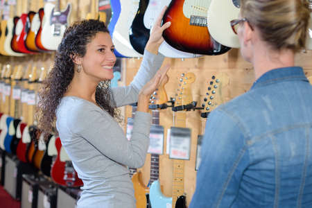 shop keeper: Keeper of musical instrument shop selecting guitar for customer Stock Photo