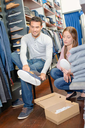 Couple in clothes shop, man trying on shoes