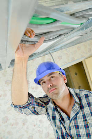 concealed: Builder holding cables at ceiling level