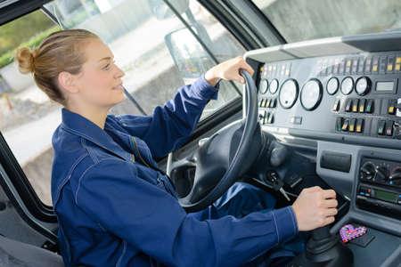 Vrouw die zware vrachtvoertuig drijft Stockfoto