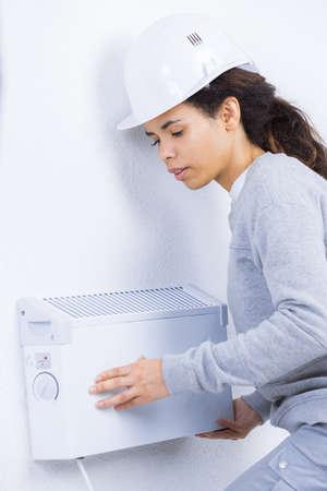 warmness: Woman fitting radiator to wall Stock Photo
