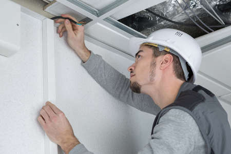 Man marking position of cable trunking