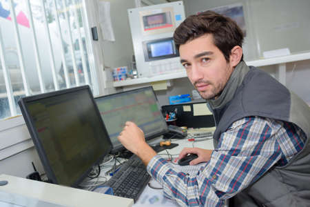 interrupted: Portrait of man using computer in site office Stock Photo