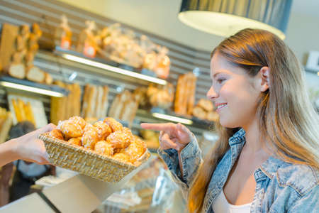 spongy: Lady pointing to little cakes in a bakery Stock Photo