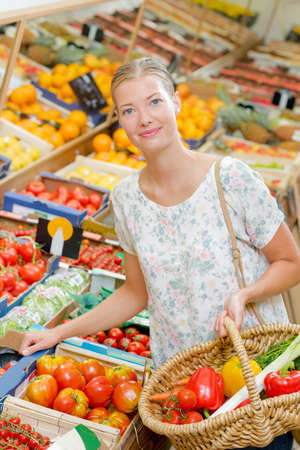 lady in grocers choosing fruit and vegetables Stock Photo