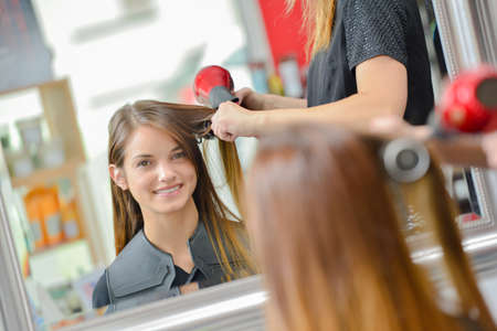 Lady having hair blow dried, looking at reflection in mirror