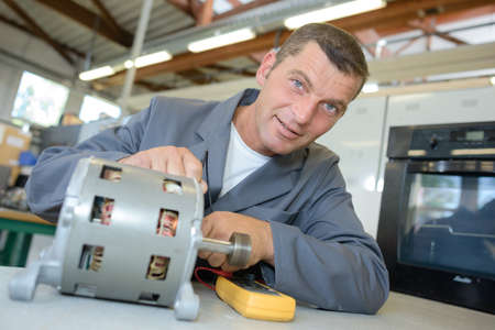 Portrait of repairman testing cylindrical component
