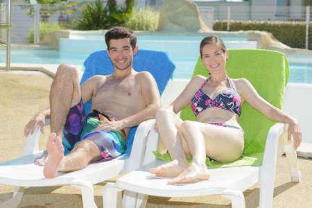 young couple lying on sunbeds Stock Photo