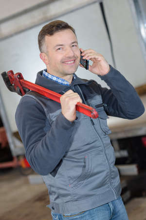 handyman talking on the phone and holding a wrench smiling