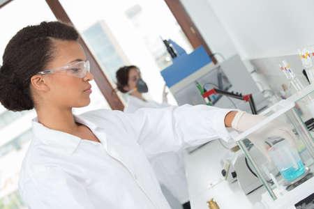 balanza de laboratorio: trabajador de laboratorio poniendo frasco de líquido en la máquina Foto de archivo