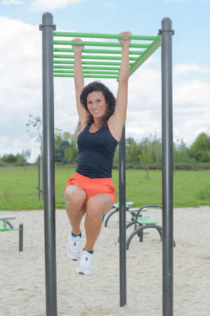 gripping bars: Woman climbing along monkey bars