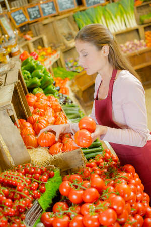 sorting out: Shop assistant sorting out tomatoes