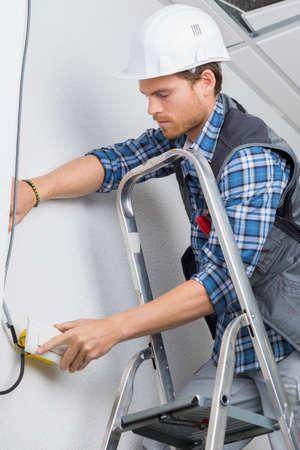 elektrische arbeider bedrading in plafond Stockfoto
