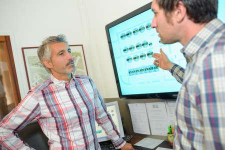 business disagreement: Men discussing display on computer screen
