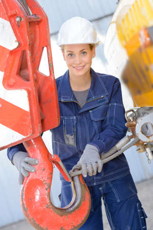 attaching: Woman attaching wire to hook of crane Stock Photo