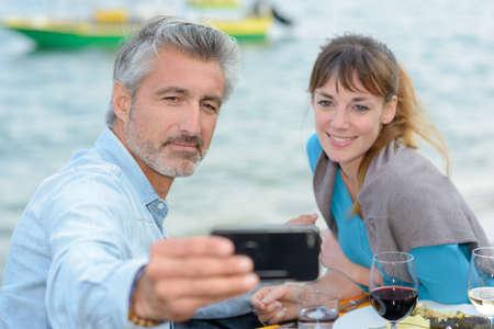 Couple taking self portrait photograph with telephone 免版税图像