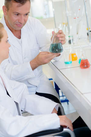 theorize: chemists mixing solutions Stock Photo
