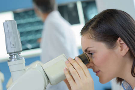 eyepiece: Woman looking into microscope