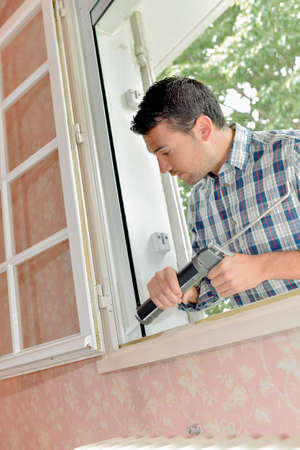 refurbish: man fixing window Stock Photo