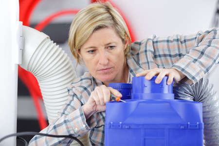 female electrician performing work on machine Stock Photo