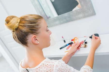 bollos: Mujer rubia que usa maquillaje Foto de archivo