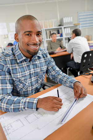amend: Smiling man working on plans Stock Photo