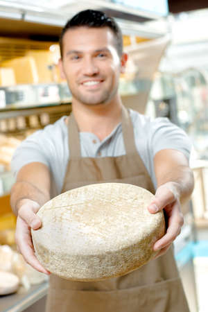 Shop worker holding circular cheese in outstretched arms