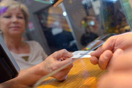 Customer nemen ticket van onder glas doorgeefluik