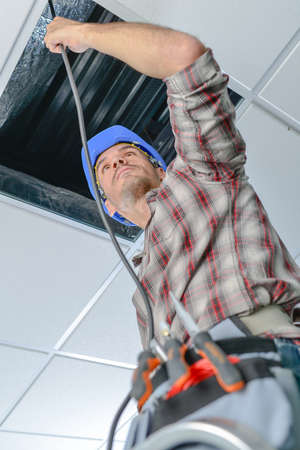 Electrician repairing wiring in an office Stock Photo
