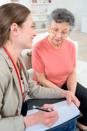 chats: Doctor taking notes as she chats to senior patient