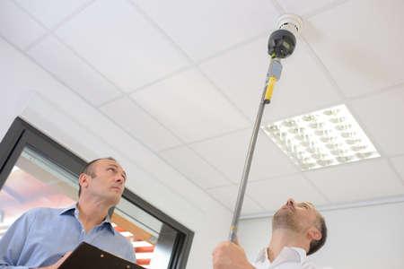 inspecting smoke alarms Stock Photo - 73345024