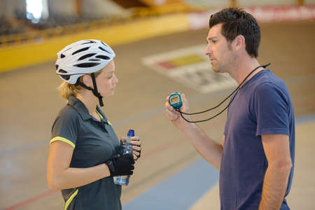 dismay: Unsatisfied coach showing stopwatch to cyclist