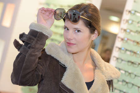Woman in flight jacket and aviator sunglasses